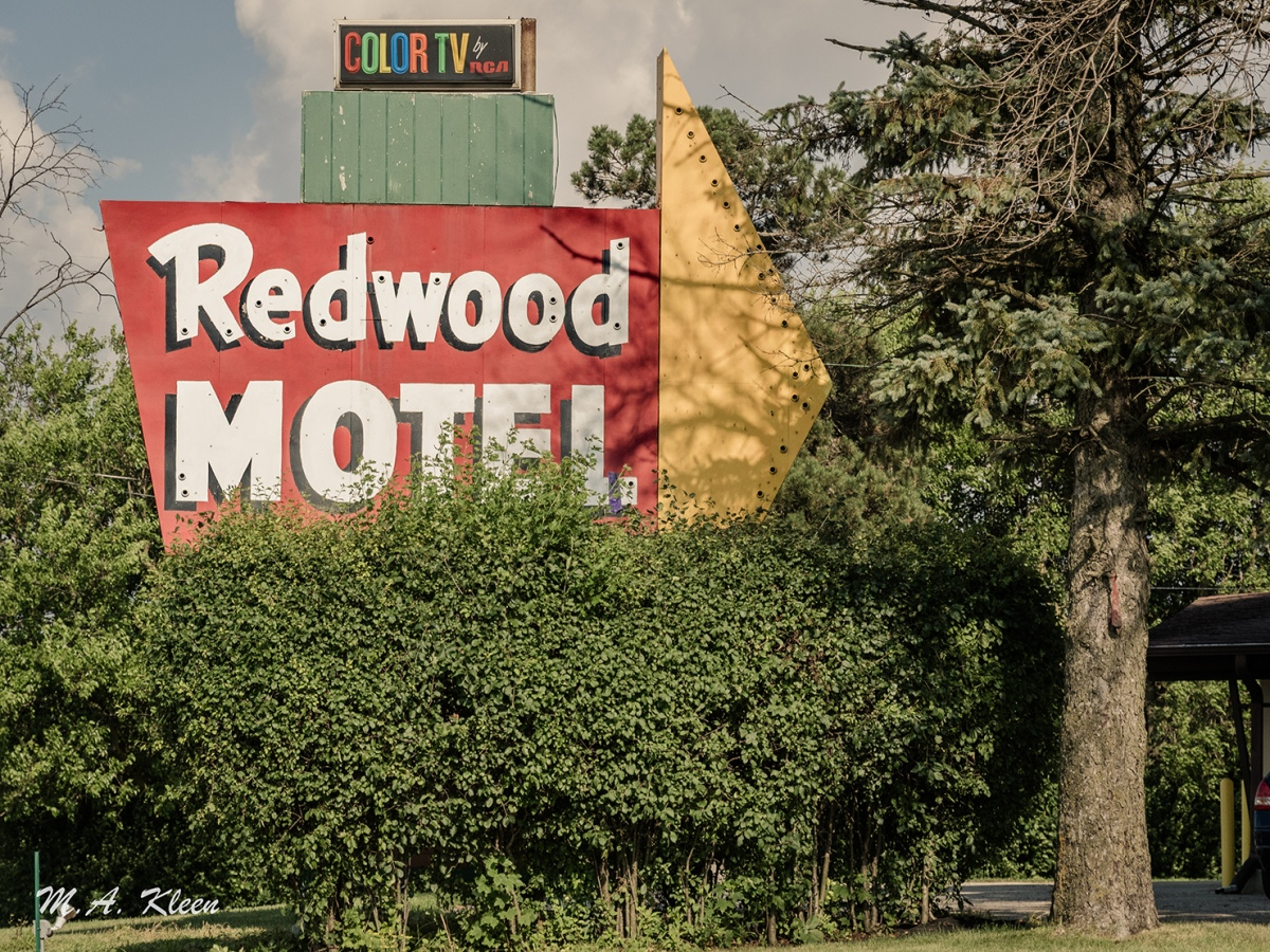 This vintage motel sign, at 3912 N. Hackbarth Road (off U.S. Route 14) outside Janesville, Wisconsin, is partially hidden behind bushes and looks to be missing its neon lights.
