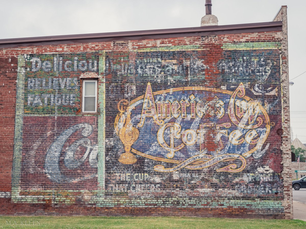 Ghost sign for America's Cup Coffee superimposed over a Coca-Cola sign on the side of Pat's Lounge, 2019 Western Avenue in Mattoon, Illinois.