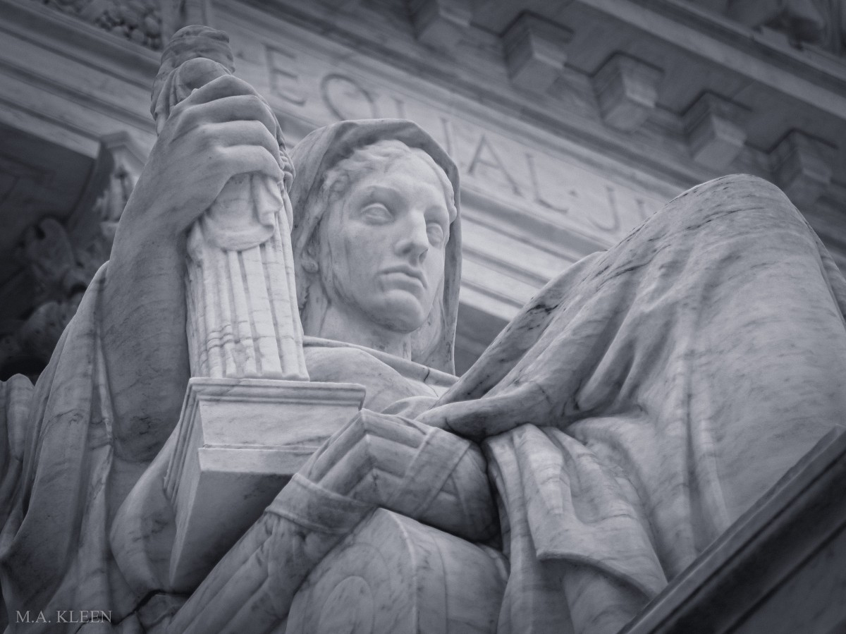 Statue outside the U.S. Supreme Court, 1 First Street NE in Washington, DC. 'Contemplation of Justice' by sculptor James Earle Fraser depicts a female figure in meditation while holding a book of law in one hand and a figure of Justice in the other.